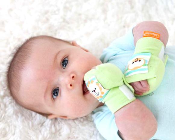 Новорожденный жует свои руки